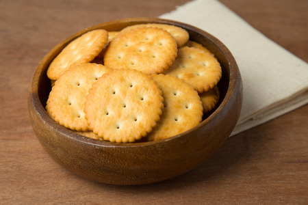 Round salted cracker cookies in wooden bowl putting on linen and wooden background.