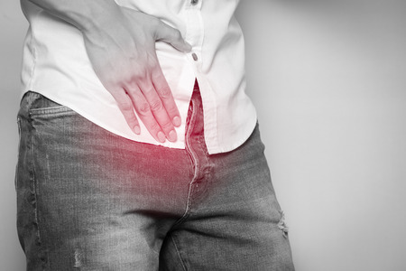 Male hands holding on middle crotch of trousers with prostate inflammation, Prostate cancer, Mens health care concept.