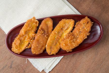 Fried bananas in wooden plate on white linen, Kluay Tod - Thai dessert.