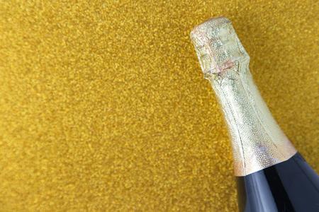 Champagne bottle on gold glitter background, Celebration concept.