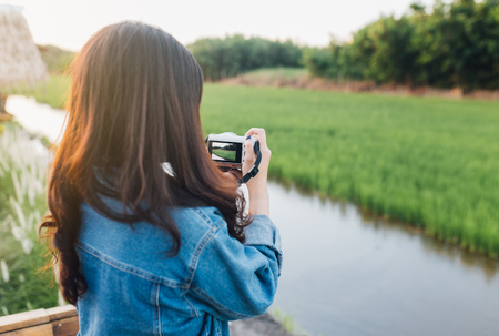 Young asian woman smiling. Girl using camera and enjoying at beautiful nature with sunset. Travel Summer Holiday Vacation and Relaxation concept. Imagens