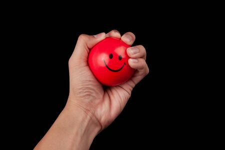 Hand squeezing a red stress ball isolated on black background 版權商用圖片 - 150279200