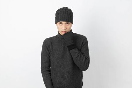 Young handsome asian man wearing grey sweater and beanie trembling, shaking from cold wind, freezing on white background.