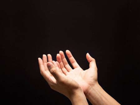 Praying hands in the dark background with faith in religion and belief in God. Standard-Bild
