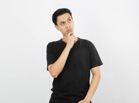 Young handsome asian man thinking an idea while looking up isolated on white background. Standard-Bild