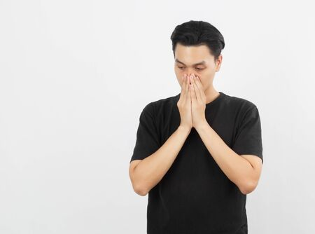 Young handsome asian man with black shirt unhappy with hands covering mouth isolated on white background.