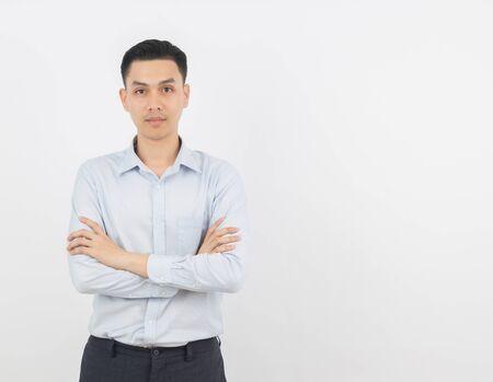 Młody przystojny azjatycki biznes człowiek patrząc na kamery z rękami skrzyżowanymi na białym tle.
