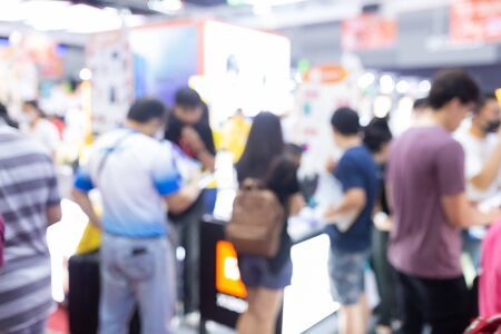 Abstract blur people in exhibition hall event trade show expo background. Business convention show, job fair, or stock market. Organization or company event, commercial trading, or shopping mall marketing advertisement concept.