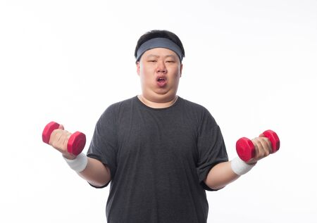 Asian Funny Fat Man in sport outfits exercising with dumbbells and looking to camera isolated on white background. Stock Photo