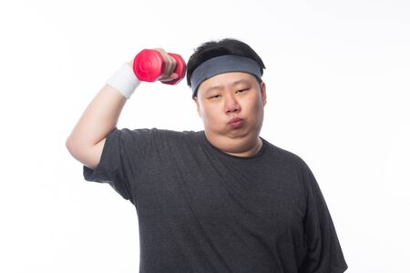 Asian funny fat man in sport outfits exercising with dumbbell and looking to camera isolated on white background.