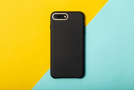 Black blank leather smartphone case on yellow half blue background.