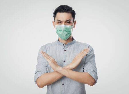 Young Asian businessman wearing hygienic mask gesturing stop to prevent infection, 2019-nCoV or coronavirus. Airborne respiratory illness such as pm 2.5 fighting and flu. Studio shot isolated on white background. Stock Photo