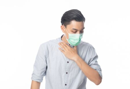 Young Asian Businessman in hygienic mask suffering sore throat, 2019-nCoV or coronavirus. Airborne respiratory illness such as pm 2.5 fighting and flu. Studio shot isolated on white background. Stock Photo