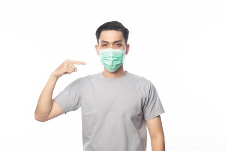 Young Asian Man wearing and pointing to hygienic mask to prevent infection, 2019-nCoV or coronavirus. Airborne respiratory illness such as pm 2.5 fighting and flu. Studio shot isolated on white background.