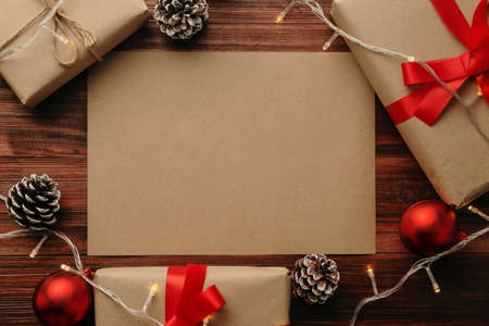 Christmas and new year with gift box wrapped with kraft brown paper and red ribbon on wooden table background top view.
