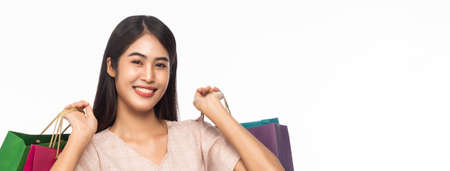 Portrait of smiling beautiful asian woman wearing dress and holding shopping bags isolated on white banner background.