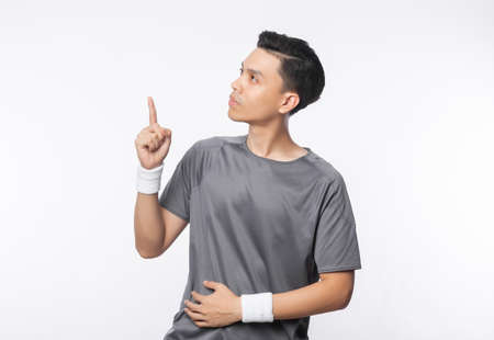 Young handsome asian sport man pointing to copy space isolated on white background.