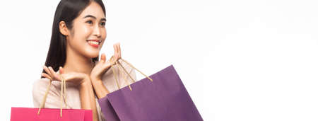 Portrait of an excited beautiful asian woman wearing dress and holding shopping bags isolated on white banner background. 版權商用圖片