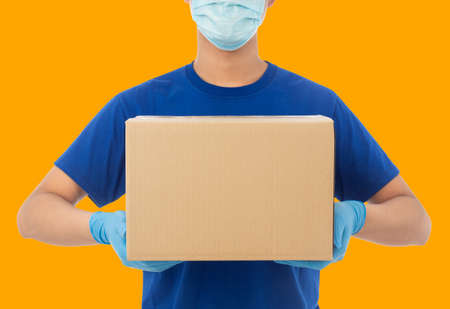 Delivery man hand in medical gloves and wearing mask holding cardboard box mockup template, Delivery service concept. Zdjęcie Seryjne