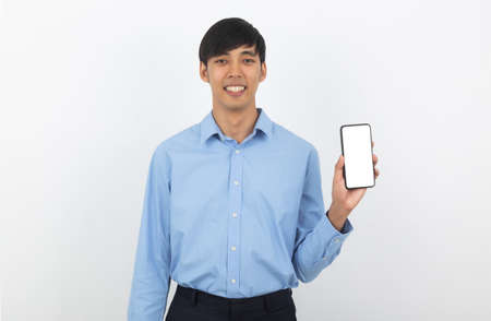 Young handsome asian business man showing smartphone with blank screen and smiling isolated on white background.