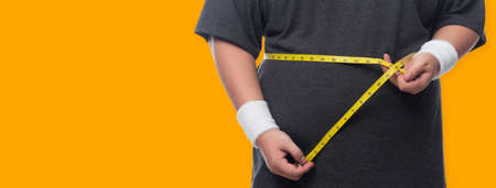 Fat man holding a measurement tape for check out his body on colorful orange banner background with copy space.