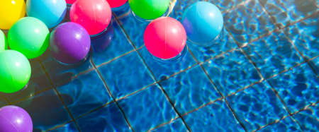 Colorful balls in swimming pool in the morning with copy space, Summer, vacation and relaxing concept. Banner background 版權商用圖片