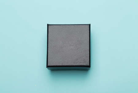 Mini black box product packaging isolated on blue background. Flat lay Top view.