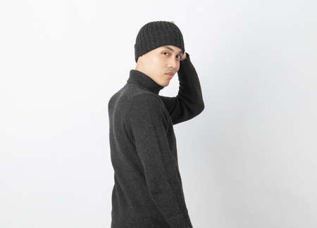 Young asian man wearing grey sweater and beanie while looking to camera with happy face on white background.