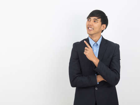 Happy smiling asian businessman in black suit pointing to copy space isolated on white background, Business success concept. 版權商用圖片