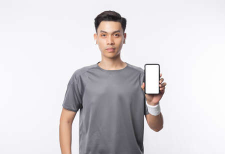 Young handsome asian man in sport outfits showing phone with blank screen and listening music isolated on white background.
