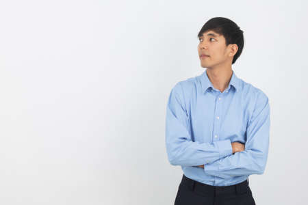 Young handsome asian business man thinking an idea while looking up isolated on white background.