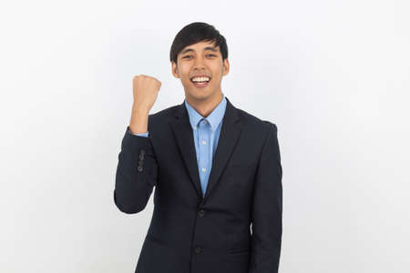 Excited young handsome asian business man raising his fists with smiling, celebrating success isolated on white background.