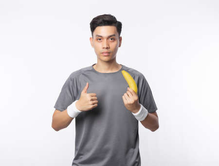 Young handsome asian sport man holding banana and showing thumbs with smiling isolated on white background. Healthy lifestyle concept.