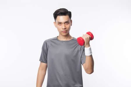 Young handsome asian man in sport outfits exercising with dumbbell and looking to camera isolated on white background.