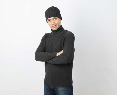 Young handsome asian man wearing grey sweater and beanie while arms crossed and looking to camera with happy face on white background. 版權商用圖片