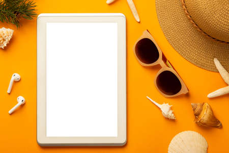Summer background with blank screen tablet computer and beach accessories - sunglasses, straw hat on vibrant orange background top view with copy space.