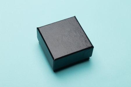 Mini black box product packaging isolated on blue background. 版權商用圖片