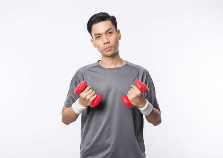Young asian man in sport outfits exercising with dumbbells and looking to camera isolated on white background.