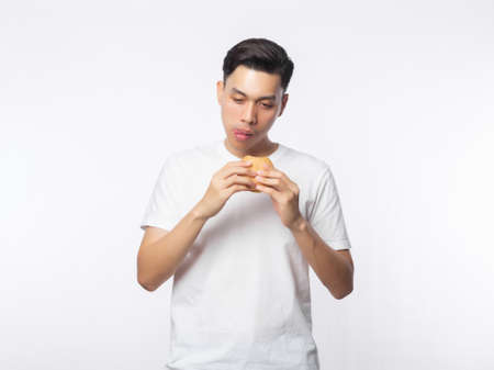 Young asian man in white t-shirt eating hamburger with happy face isolated on white background. 版權商用圖片