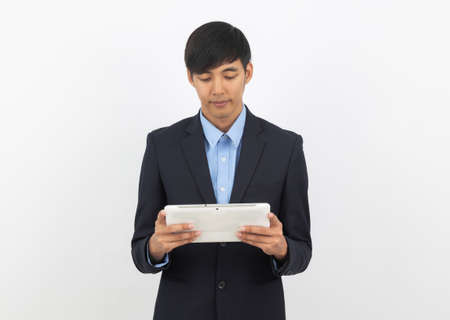 Young handsome asian business man using tablet computer with smiling isolated on white background. 版權商用圖片