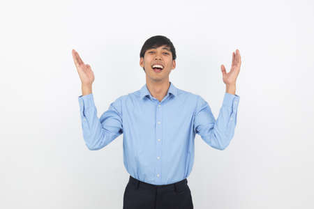 Excited young business Asian man raising his fists with happy delighted face, celebrating success isolated on white background.