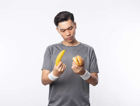 Young asian man in sport outfits holding banana and hamburger with doubts face isolated on white background.