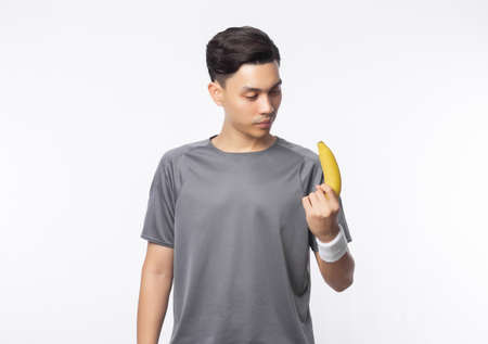 Young handsome asian sport man holding banana with smiling isolated on white background. Healthy lifestyle concept.
