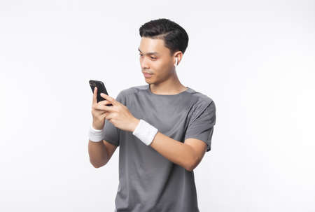 Young handsome asian man in sport outfits using phone and listening music with smiling isolated on white background. 版權商用圖片