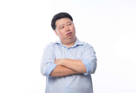 Asian fat man in blue shirt arms crossed and looking to copyspace isolated on white background.