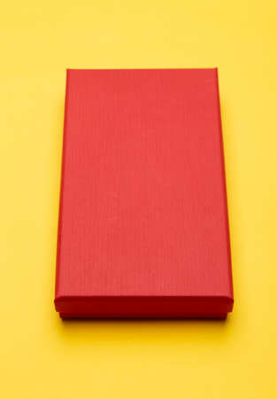 Red box product packaging isolated on yellow background. 版權商用圖片