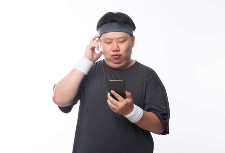 Young Asian funny fat sport man using smartphone listening music isolated on white background.