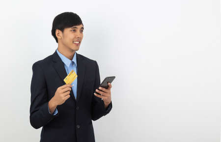 Young handsome asian business man using smartphone for online payment with smiling isolated on white background. 版權商用圖片