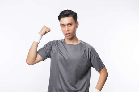 Young handsome asian sport man showing strenght and looking to camera isolated on white background.