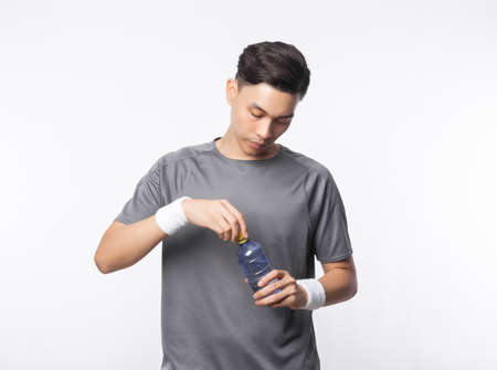 Young handsome asian sport man holding water bottle with smiling isolated on white background. Healthy lifestyle concept.